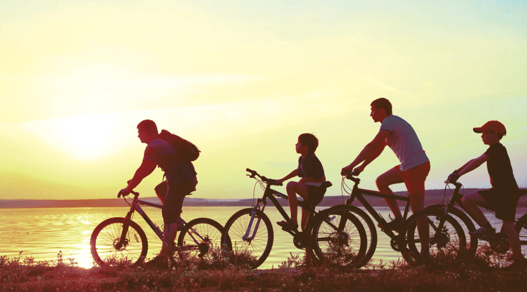 Family on bikes at sunset